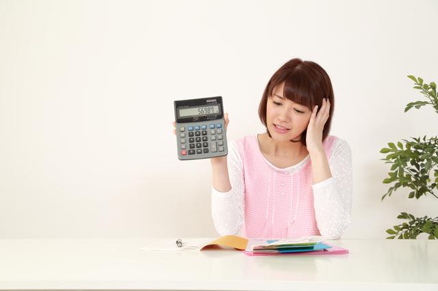 電卓を持って計算に悩んでいる女性
