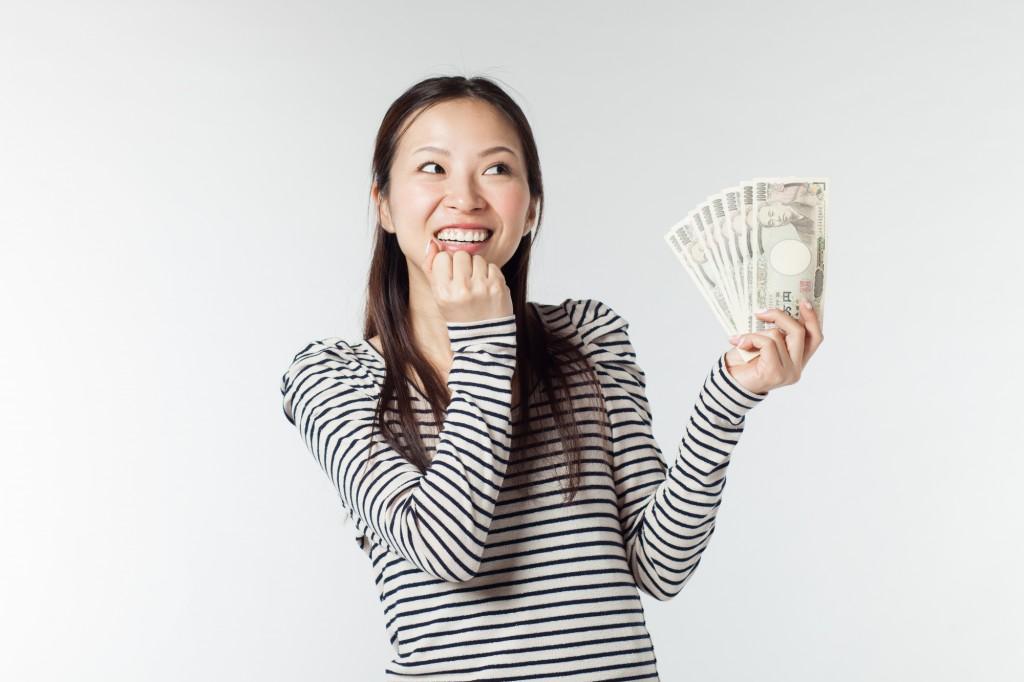 お金を持って嬉しそうな女性