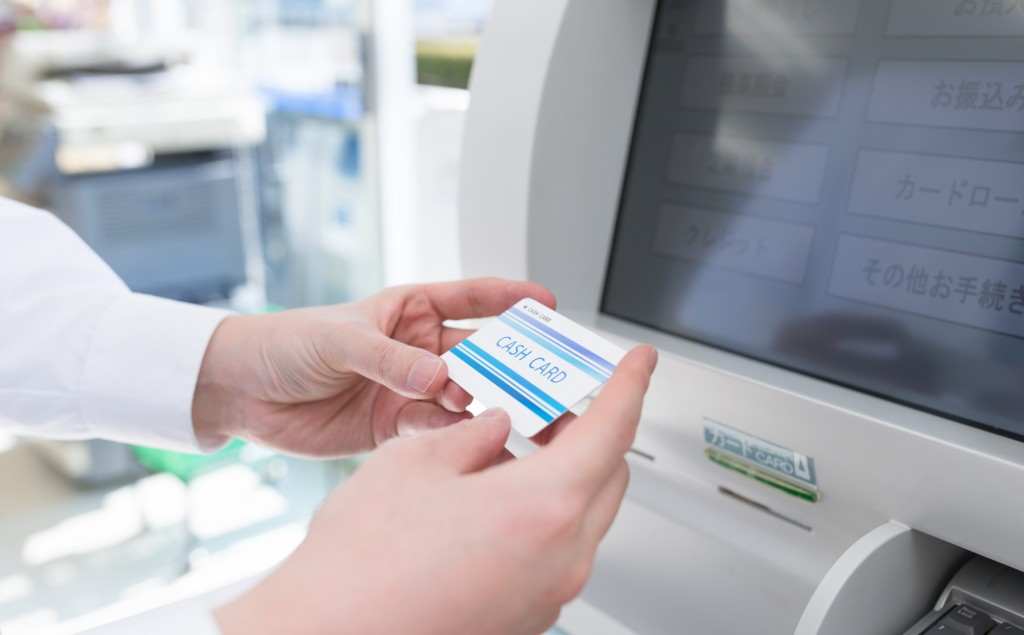 ATMの前でカードを持つ男性