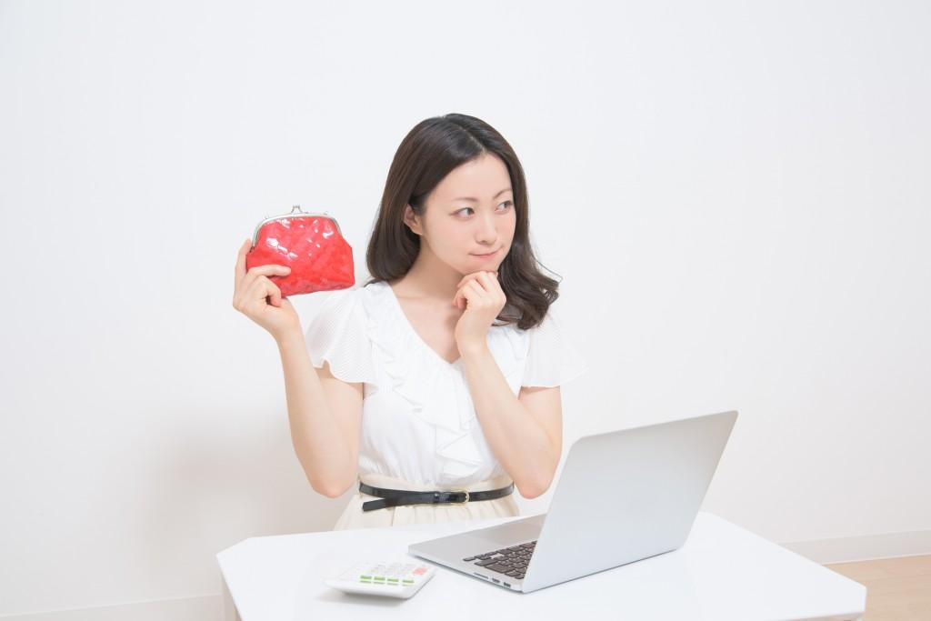 パソコンの前で財布をもって喜ぶ女性