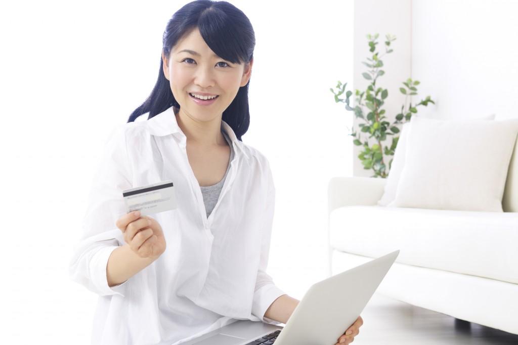 パソコンとカードを持つ女性