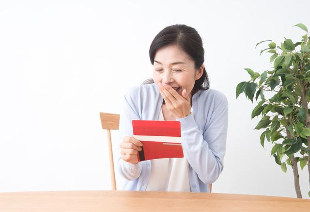 預金通帳を見て喜ぶ主婦