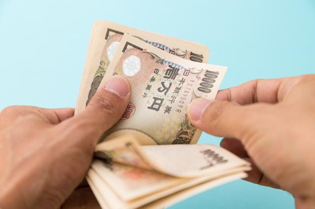 お金を数える男の手の写真