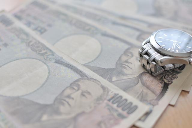 お金と腕時計の写真